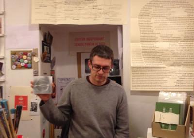 Présentation du DVD <i>Vases communicants canopes</i> par Nicolas Tardy, lors du lancement des posters de Alain Cressan et de Pierre Ménard samedi 15 novembre 2014 à la Librairie Le Lièvre de Mars, à Marseille.